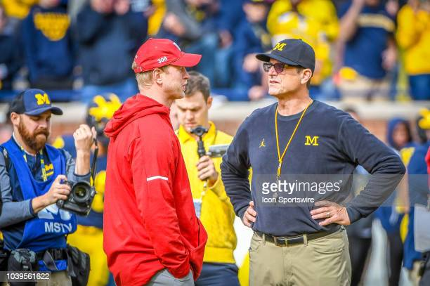 Nebraska Cornhuskers head coach Scott Frost and Michigan Wolverines head coach Jim Harbaugh talk during pregame warm ups prior to the Michigan...