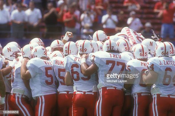 Nebraska Cornhuskers huddle before a college football game against the West Virginia Mountaineers on August 31, 1994 at Giants Stadium in East...