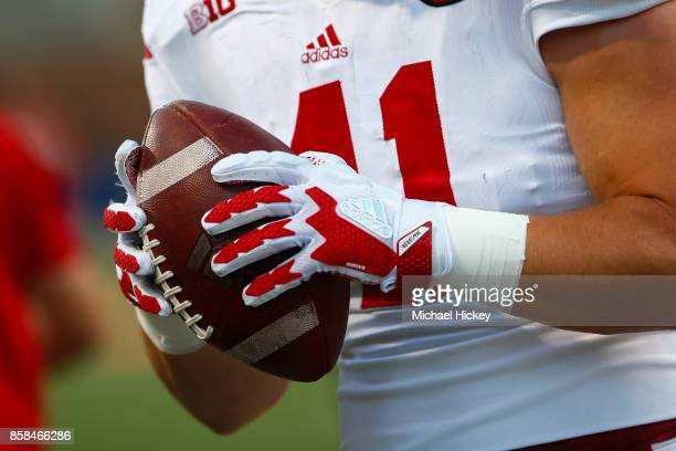 Nebraska Cornhuskers player wearing Adidas gloves grips the football during warmups before the game against the Illinois Fighting Illini at Memorial...