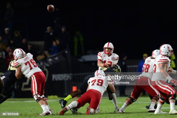 Nebraska Cornhuskers quarterback Tanner Lee is hit as he releases the ball during the Big Ten conference game between the Purdue Boilermakers and the...
