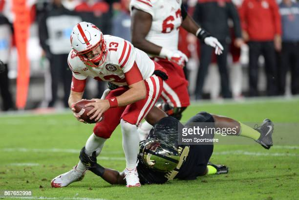 Nebraska Cornhuskers quarterback Tanner Lee struggles to break free from the tackle of Purdue Boilermakers defensive end Gelen Robinson during the...