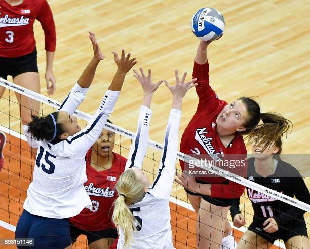 Nebraska outside hitter Mikaela Foecke hits the ball past Penn State middle blocker Haleigh Washington and outside hitter Ali Frantti in the first...