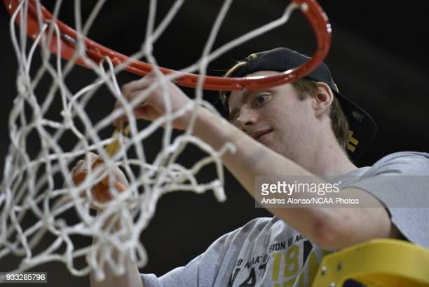 Nebraska Wesleyan Prairie Wolves guard Austin Hall cuts down the net after the Prairie Wolves win their first Division III Men's Basketball...