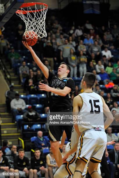 Nebraska Wesleyan Prairie Wolves guard Nate Schimonitz drives for a basket over WisconsinOshkosh Titans forward Adam Fravert during the Division III...