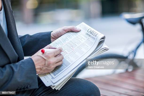 Neck down view of businessman circling job vacancies in newspaper