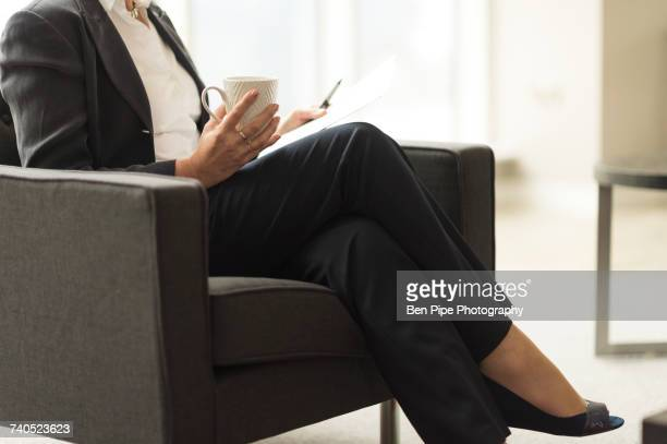 Neck down view of businesswoman sitting in office reading paperwork