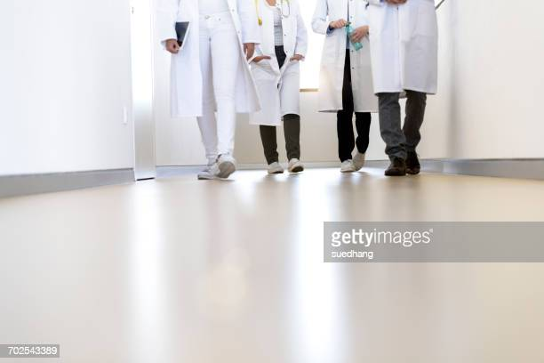 Neck down view of male and female doctors walking in hospital corridor