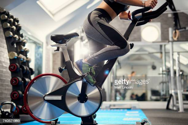neck down view of young woman training, pedalling exercise bike in gym - exercise bike stock photos and pictures