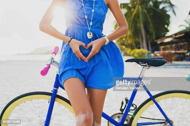 neck down view of young woman with bicycle making heart shape with hands on sandy beach, krabi, thailand - blue dress stock pictures, royalty-free photos & images