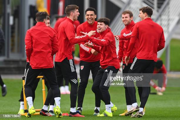 Neco Williams, Benjamin Cabango and Chris Mepham in good spirits during the Wales training session at The Vale Resort on March 29, 2021 in Vale of...