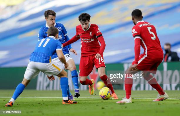 Neco Williams of Liverpool is closed down by Solomon March and Leondro Trossard of Brighton and Hove Albion during the Premier League match between...