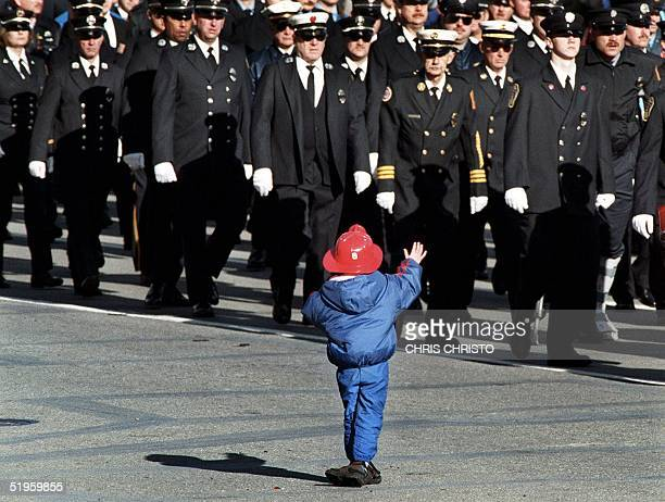 Ned Baxter waves to thousands of firefighters from around the United States as they march in a procession in downtown Worchester MA 09 December 1999...