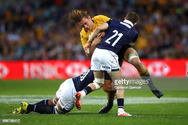 Ned Hanigan of the Wallabies is tackled during the International Test match between the Australian Wallabies and Scotland at Allianz Stadium on June...