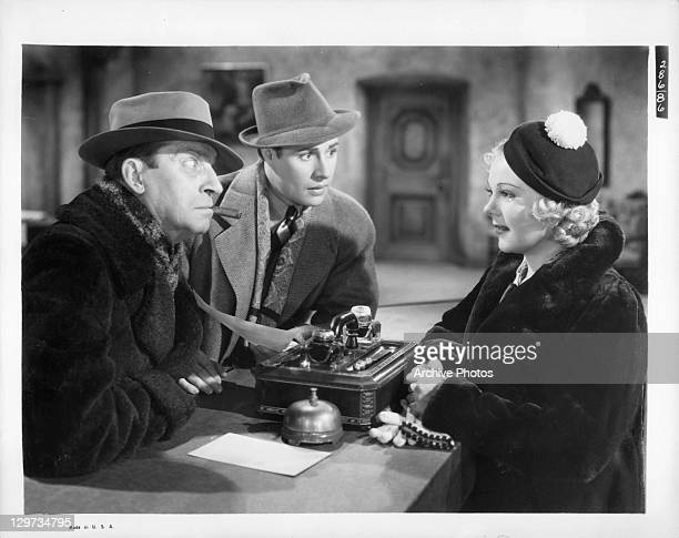 Ned Sparks and Don Ameche both stare at Sonja Henie in a scene from the film 'Happy Landing' 1938