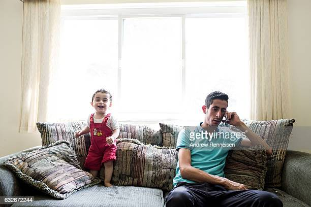 Nedal Al Hayek and his son Taym on the couch in their new home in Bloomfield Hills Michigan on July 28 2015 The family including Nedals wife Raeda...