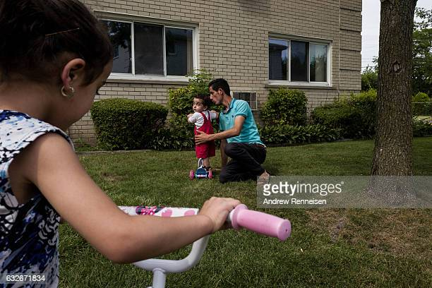 Nedal Al Hayek plays with his son Taym and daughter Layal outside their new home on July 28 2015 in Bloomfield Hills Michigan The family including...