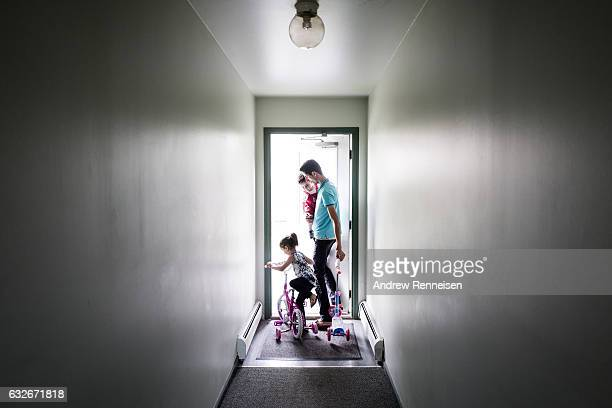 Nedal Al Hayek takes his son Taym and daughter Layal outside their new home to play on July 28 2015 in Bloomfield Hills Michigan The family including...