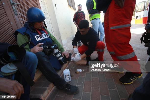 Nedal Eshtayah a freelance photojournalist to Turkey's Anadolu Agency receives firstaid by paramedics after he was wounded during the Israeli...