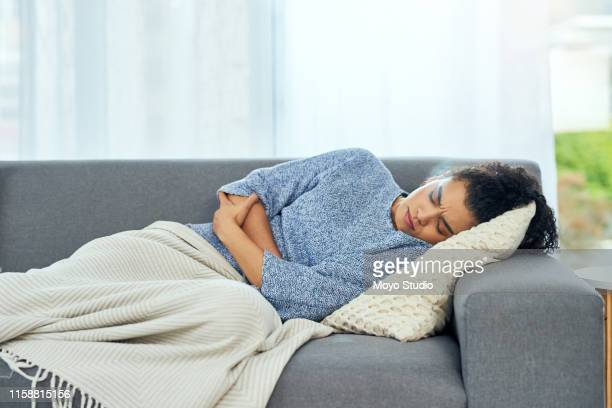 i need painkiller and a hot water bottle - menstruation stock pictures, royalty-free photos & images