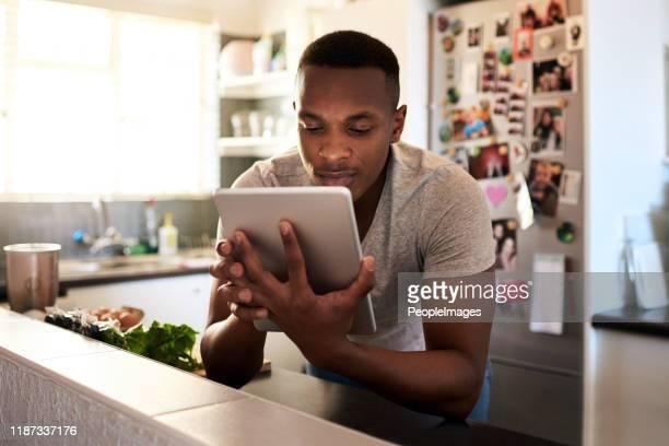 ik moet een aantal goede kookvideo's vinden - een tablet gebruiken stockfoto's en -beelden