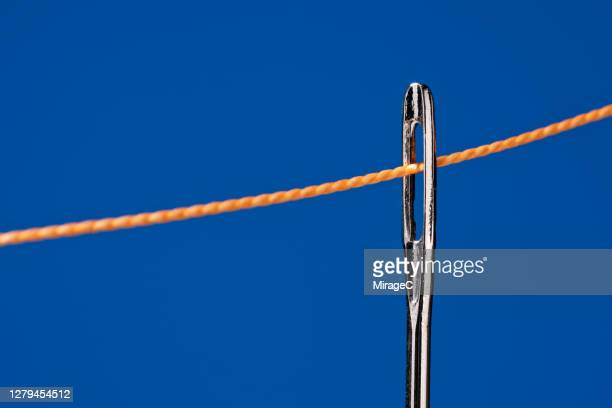 needle and thread on blue - things that go together stock pictures, royalty-free photos & images