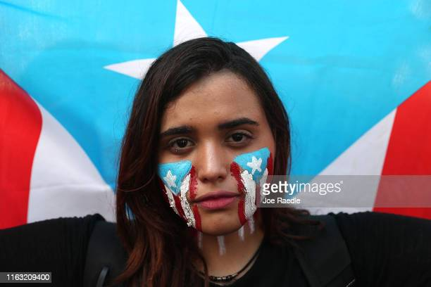 Neelete Coss joins with other protesters as they demonstrate against Ricardo Rossello, the Governor of Puerto Rico, near a police barricade set up...