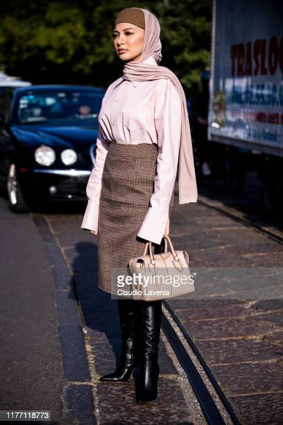 Neelofa wearing a pink leather shirt brown checked midi skirt black boots and nude Tod's bag is seen outside the Tod's show during Milan Fashion Week...