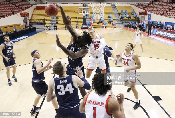 Neemias Queta of the Utah State Aggies blocks a shot by Kevin McCullar of the Texas Tech Red Raiders during the first half in the first round game of...