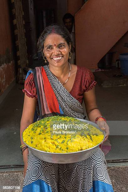 Neetha Rathore holds curried potatoes that she prepared which is used for stuffing an Indian snack that is sold by her husband on a food cart
