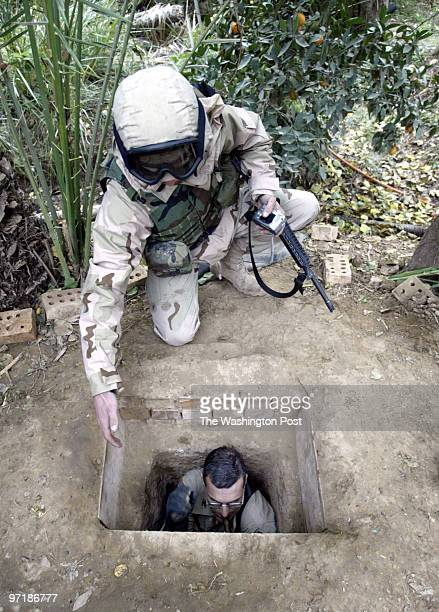 PhotogPreston Keres/TWP Dawr Iraq Sgt Jeremy Nickell kneels down to help Col Robert W Nicholson 4th Infantry Divsion Engineer climb out of the hole