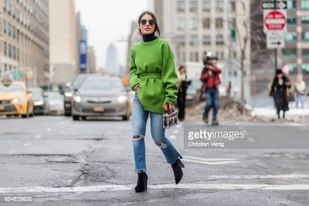 Negin Mirsalehi wearing a green knit denim jeans Louis Vuitton bag ankle boots outside Lacoste on February 11 2017 in New York City