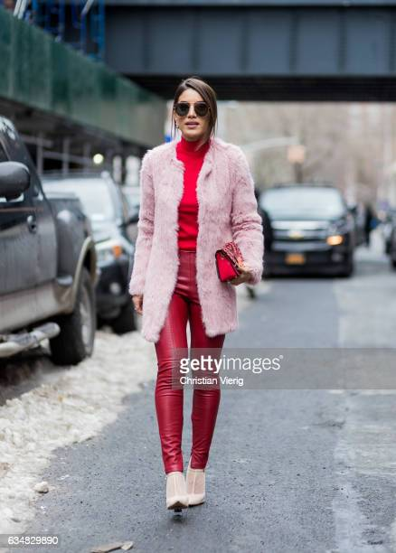 Negin Mirsalehi wearing red leather pants pink coat red knit outside Tibi on February 11 2017 in New York City