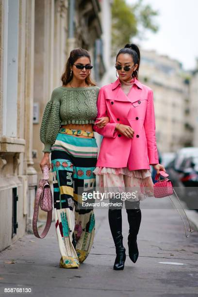 Negin Mirsalehi wears a green bare belly wool pull over colored pants Chriselle Lim wears sunglasses a pink coat a pink flower print ruffle skirt...