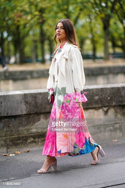 Negin Mirsalehi wears a pink, green and blue floral print cream-color top with a lavaliere, a pink, green and blue floral print cream-color pleated...