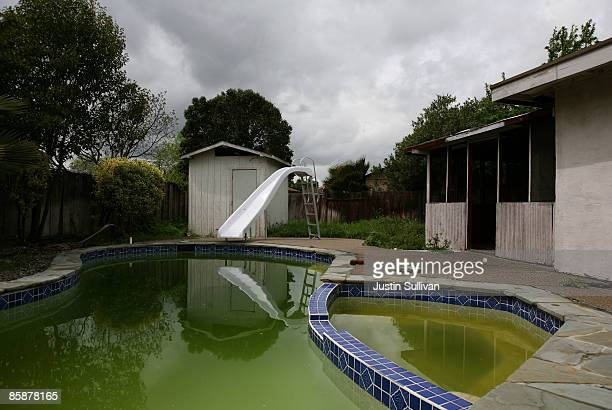 A neglected pool is green with algae at a foreclosed home April 9 2009 in Concord California Unseasonably warm weather for Northern California in...