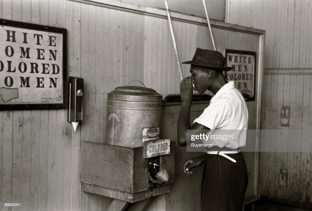 "Negro drinking at ""Colored"" water cooler in streetcar terminal, Oklahoma City, Oklahoma : News Photo"
