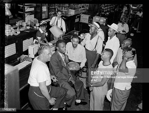 Negro League pitcher Satchel Paige seated at bar with Leonard 'Big Bill' Williams on left, and other men, in Crawford Grill No. 1, Pittsburgh,...