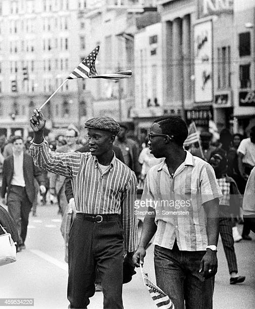 Negro teenage boys waving small American flags marching through Montgomery to Alabama State House with Selma to Montgomery marchers On March 25 1965...