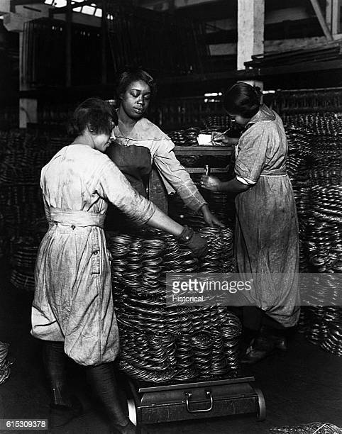 Negro women weighing wire coils and recording weights to establish wage rates April 16 1919 | Location factory