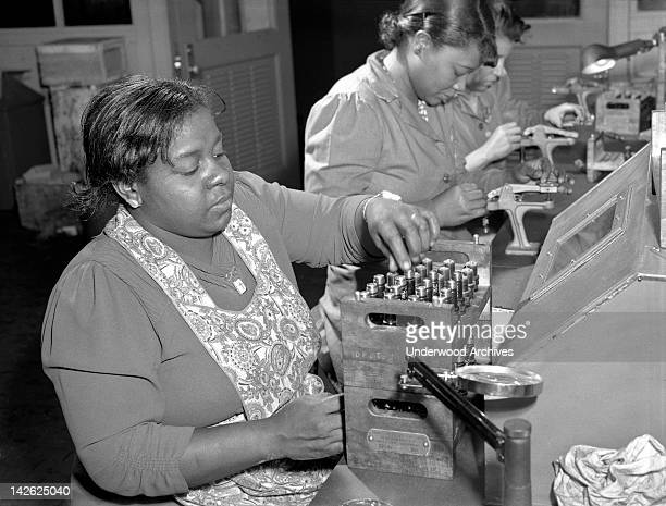 Negro women with no previous industrial experience are reconditioning used spark plugs in a converted Buick plant to produce airplane engines Melrose...