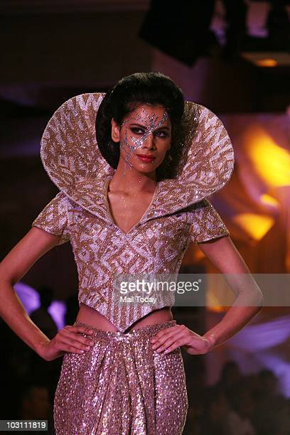 Neha Kapur walks the ramp for designers Abu Jani and Sandeep Khosla at the grand finale of the Delhi Couture Week in New Delhi on July 25 2010