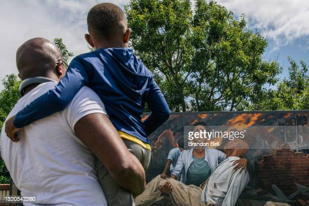 Nehemiah Frank , teaches his cousin David McIntye II of the Tulsa massacre, in the Greenwood district, on May 28, 2021 in Tulsa, Oklahoma. This year...