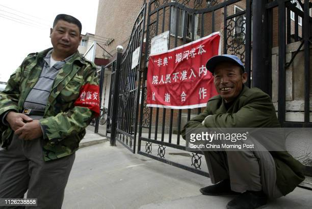 Neigbourhood security guards stand guard outside a residential area to stop nonresidents entering in Hohhot Inner Mongolia Precautions against SARS...