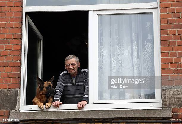 A neighbor and his dog look on during a raid off of Place General Meiser in the Schaarbeek district on March 25 in Brussels Belgium Explosions from...
