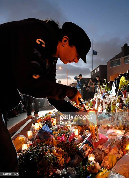 Neighbor Bernece DiCarlo lights a candle at a memorial set up in driveway of former NFL star Junior Seau's house May 3 in Oceanside Calif The former...