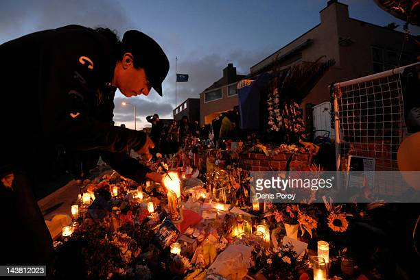 Neighbor Bernece DiCarlo lights a candle at a memorial set up in the driveway of former NFL star Junior Seau's house May 3 in Oceanside California...