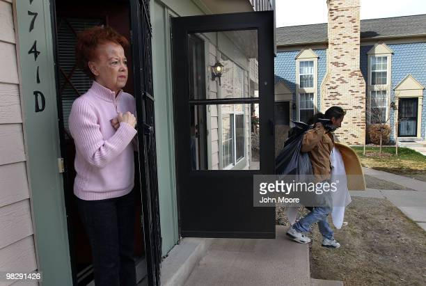 Neighbor Kathy Brown watches as an eviction team removes a family's belongings from an apartment on April 6 2010 in Aurora Colorado The tenants had...