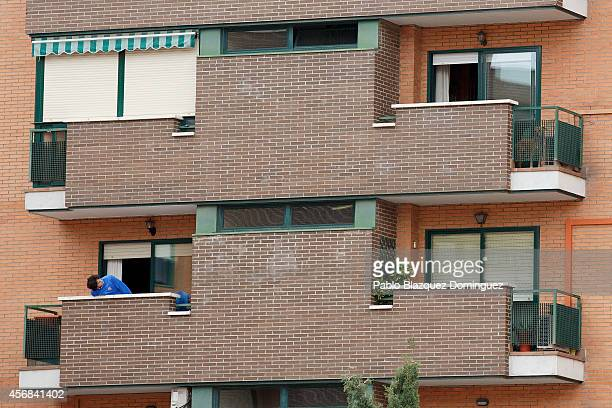 A neighbor looks at dog 'Excalibur' barking on the balcony of the private residence for Spanish nurse Teresa R R who has tested positive for the...
