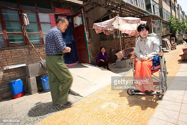 A neighbor walks pass Li Yan sitting in her wheelchair in a residence on May 7 2007 in Yinchuan Ningxia Province China 28yearold Li Yan suffers from...