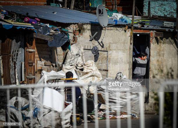 A neighbor watches from the door of his house at Villa Azul on May 26 2020 in Buenos Aires Argentina The slum remains isolated by authorities after...